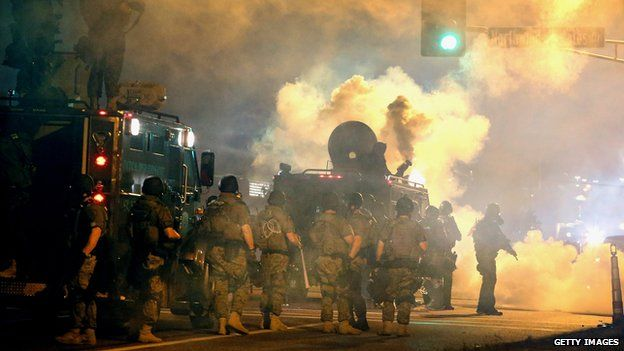 Riot police on 18 August 2014 face off with protesters angered by the killing of a black teenager by a white policeman in Ferguson, Missouri.