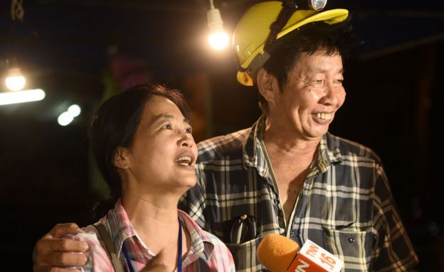 Relatives of children trapped in a cave in Thailand celebrate the entrance to it.