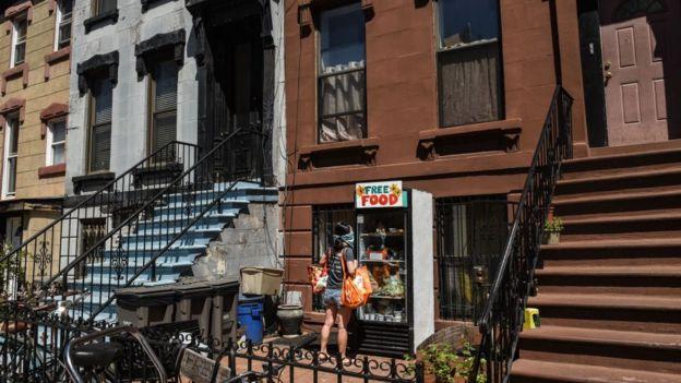Девушка перед окном раздачи бесплатной еды в Бруклине