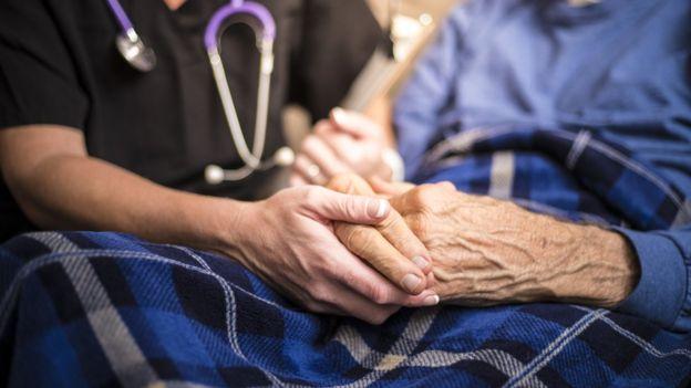 Foto de duas pessoas segurando mãos de uma das outras em um hospital