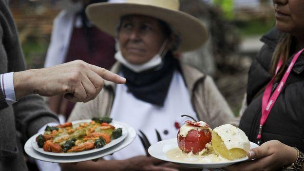 Mano de un hombre blanco y dos mujeres de origen andino frente a platos de comida.