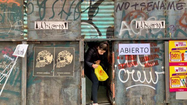 Joven saliendo de un comercio en Valparaíso