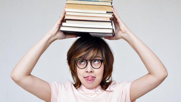 Una mujer con la lengua afuera lleva en su cabeza una pila de libros.