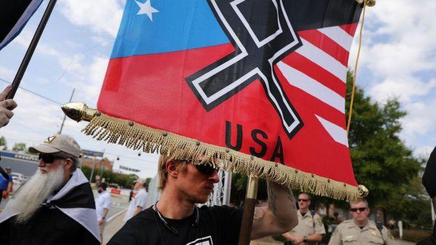 Homem segura bandeira com símbolo nazista e o nome dos EUA