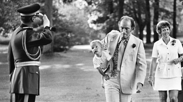 A young Justin Trudeau rests on his father's hip, 1973