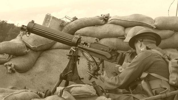 Fotografia preto e branco de dois soldados manipulando armamento pesado atrás de uma trincheira