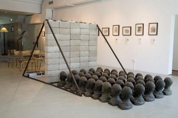 Une installation artistique comprenant des moulages de têtes, un mur de briques et une chaise, entre autres objets