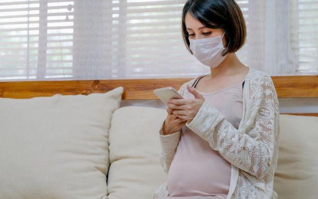 Mujer embarazada con tapabocas.