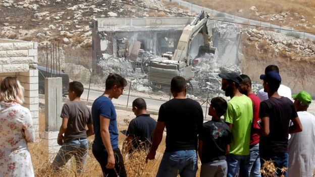 Palestinians watch Israeli army excavator demolishing a building in Wadi Hummus, in the occupied West Bank (22 July 2019)