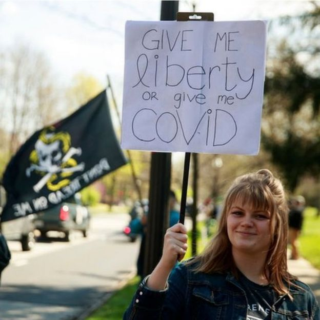 "A protester holds a placard: ""Give me liberty or give me Covid"""