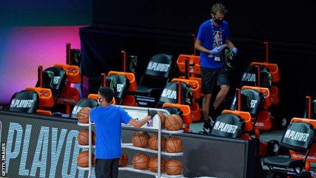 Funcionários removem itens da área do banco do Milwaukee Bucks após boicote de time