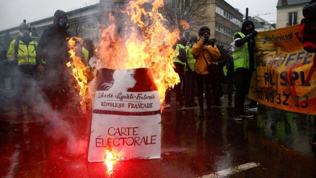 "Protesters wearing yellow vests stand near a burning facsimile voter registration card during a demonstration by the ""yellow vests"" movement in Nantes, France, 15 December."