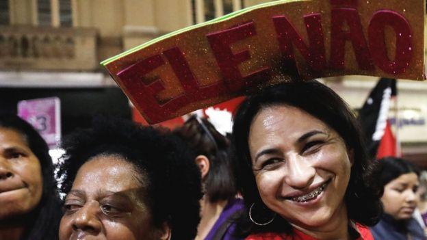 """Mulher sorri com uma placa junto ao topo da cabeça, com os dizeres """"Ele não"""", em evento de campanha do PT em São Paulo"""