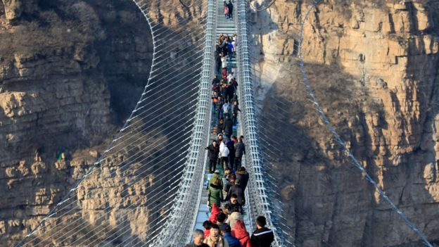 Tourists walk on the glass-bottomed suspension bridge at Hongyagu Scenic Area on December 26, 2017 in Pingshan, Hebei Province of China.