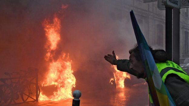 Yellow vest protester gesturing at a burning car