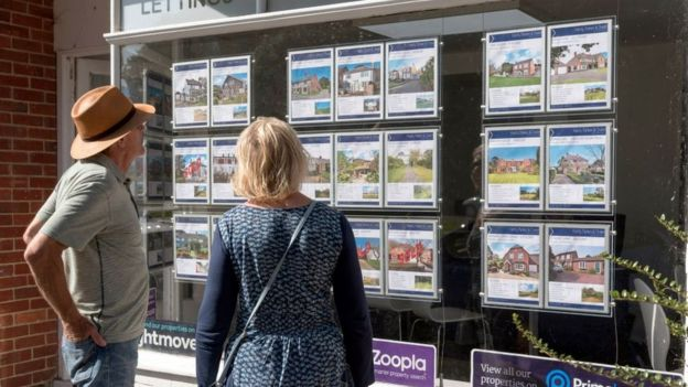 People looking at estate agent's window