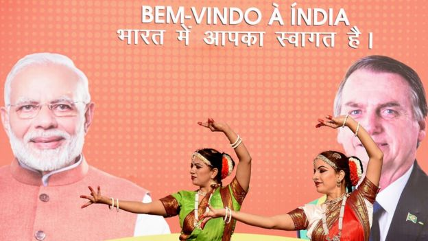 Duas dançarinas com trajes tradicionais fazem movimento em frente a painel com fotos de Narendra Modi e Jair Bolsonaro, além dos dizeres: 'Bem-vindo à Índia'