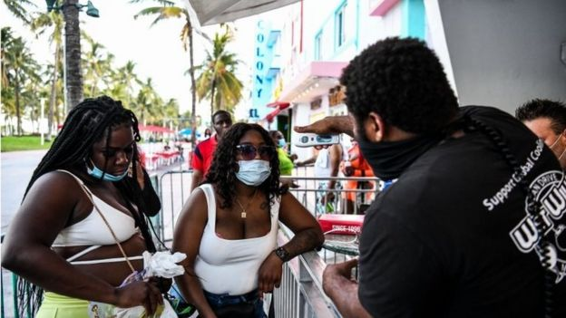 A security guard checks the temperature of a woman at the entrance of a restaurant on Ocean Drive in Miami Beach, Florida on June 24, 2020