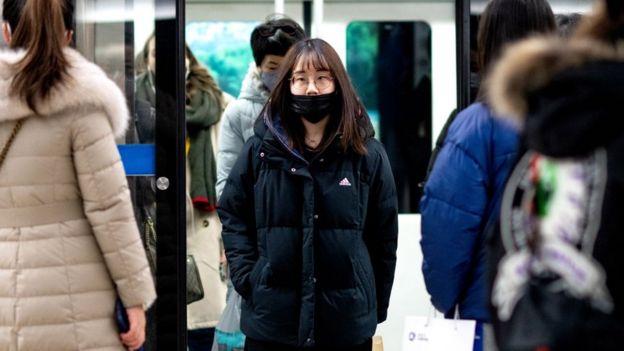 Mujer con mascarilla en el metro de Pekín, China.
