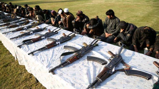 Membros do Talebã e Estado Islâmico escondemo os rostos diante de mesa com diversas armas enfileiradas
