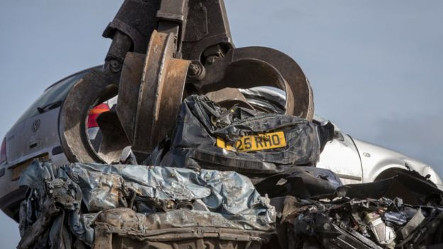 Car in claw at scrapyard