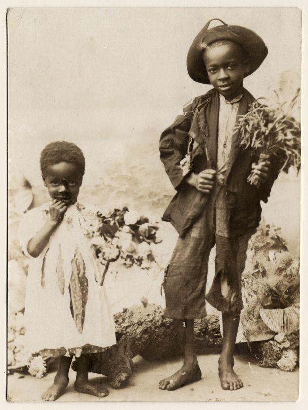 Imagem mostra duas crianças alforriadas. Elas estão de pés descalços e vestidas, segurando ramalhetes de flores e olhando para a câmera de Virgílio Calegari, um fotógrafo italiano que instalou um estúdio na capital gaúcha. Crédito: Acervo do Museu de Porto Alegre Joaquim Felizardo/Virgílio Calegari