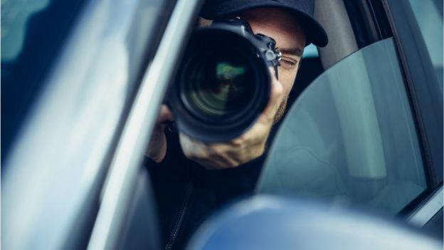 Hombre sujetando una gran cámara de fotos