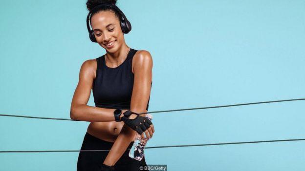 Mulher com garrafa de água na mão se exercitando