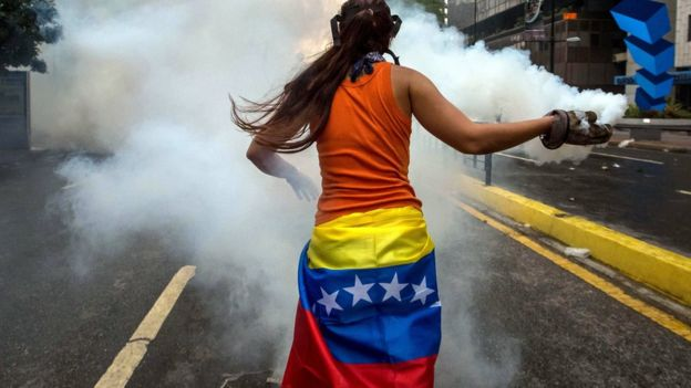 manifestante brasileña devuelve un gas.