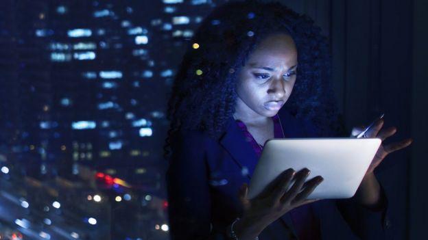 Mulher olha para tablet com o rosto iluminado pela tela
