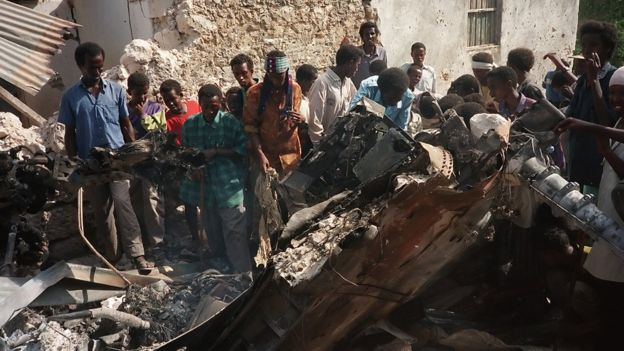 Somalis look at the wreckage of a US helicopter, in a Mogadishu street, 4 October 1993, after it was shot down.