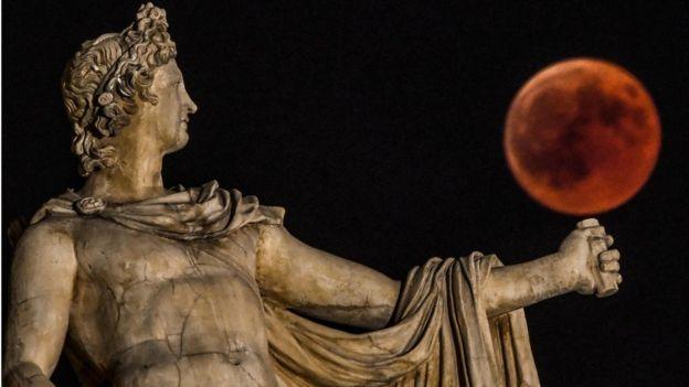 Luna de sangre y dios Apollo en Atenas, julio 27 de 2018.