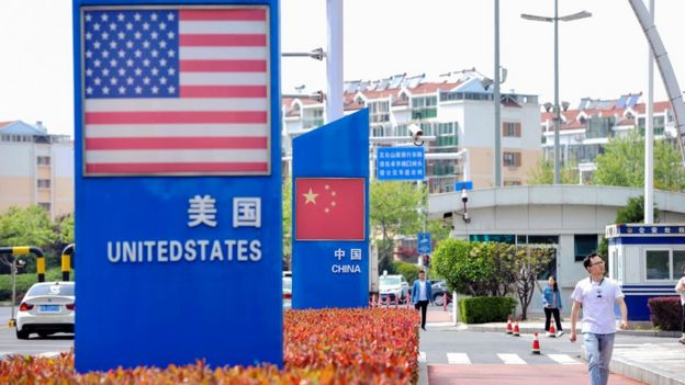 Signs with the US flag and Chinese flag are seen at the Qingdao free trade port area in Qingdao in China's eastern Shandong province on May 8, 2019.