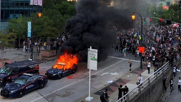 A police car burns in Atlanta, Georgia, as people protest against the death in Minneapolis police custody of African-American man George Floyd