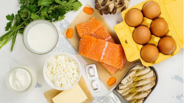 Salmão, ovos, peixe enlatado e outros alimentos que são fonte de vitamina D sobre a mesa
