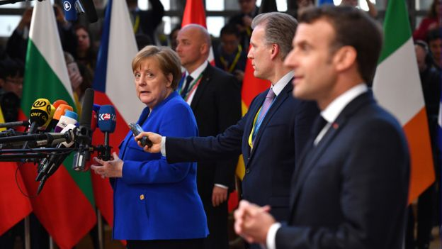 Germany's Chancellor Angela Merkel looks back at French President Emmanuel Macron as they speak to the media