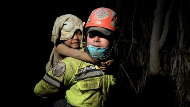 Una mujer carga a una niña