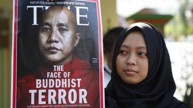 """أحد المتظاهرات تحمل صورة ويراثو ولافتة كتب عليها """"وجه الإرهاب البوذي"""" أثناء مظاهرة في جاكرتا"""