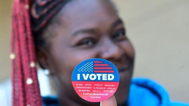 Mujer muestra su pegatina de que votó.
