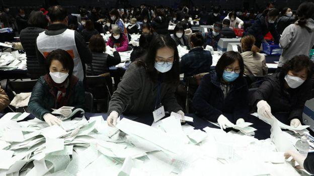 Funcionários do Comitê Central de Eleições da Coréia do Sul e observadores de eleições contam votos
