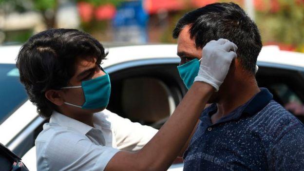 Un voluntario en India ayuda a un hombre con una mascarilla.