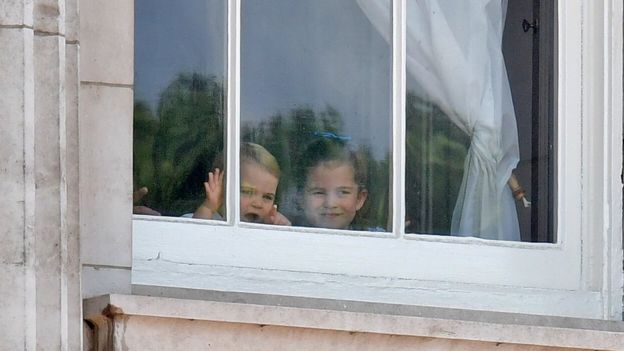 Prince Louis and Princess Charlotte peer out of the windows of Buckingham Palace during the Trooping the Colour parade