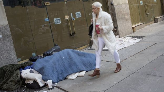 A woman walks past a homeless person sleeping on the street on March 11, 2019 in midtown Manhattan, New York City.