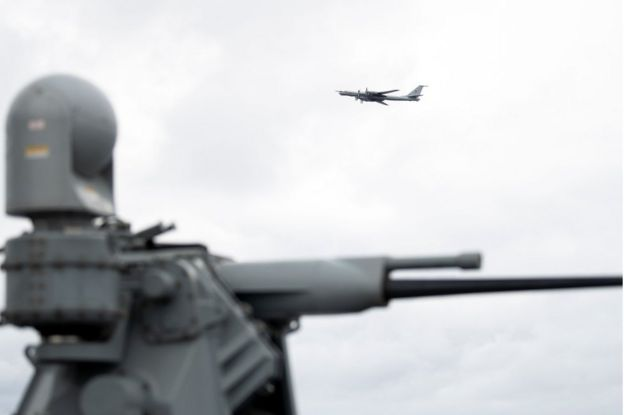 A Russian Tupolev TU-142 flies by the USS Mount Whitney of the US Navy during the NATO-led military exercise Trident Juncture on November 2, 2018 at the Norwegian sea outside Trondheim, Norway