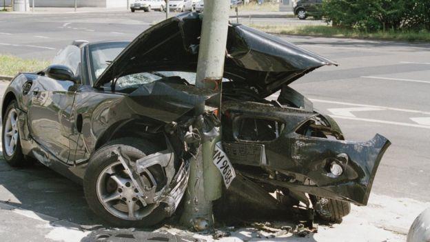 Automóvil chocado contra un poste en la calle.