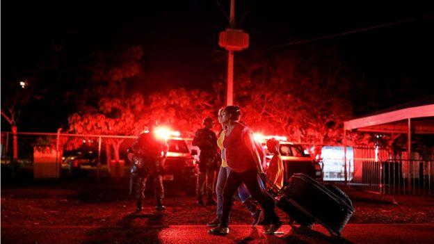 À noite, mulheres passam com malas em frente a agentes de segurança e viaturas