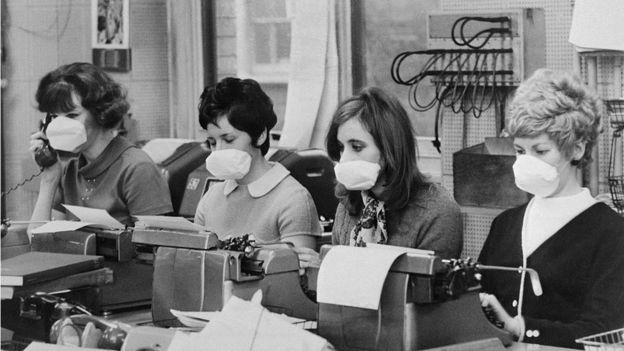 Secretarias en sus puestos de trabajo con mascarillas
