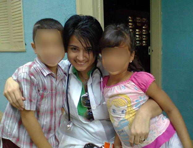 Dayli na Venezuela ao lado de duas crianças