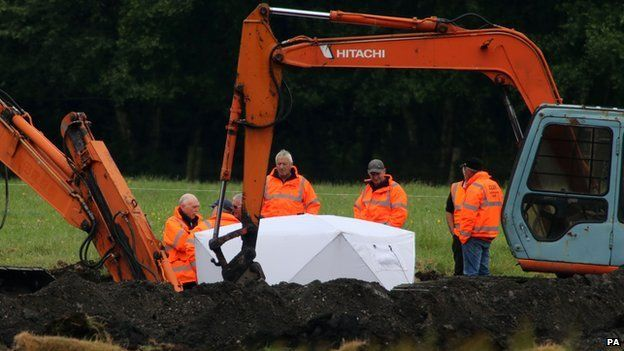 Members of the Independent Commission for the Location of Victims' Remains work at the scene