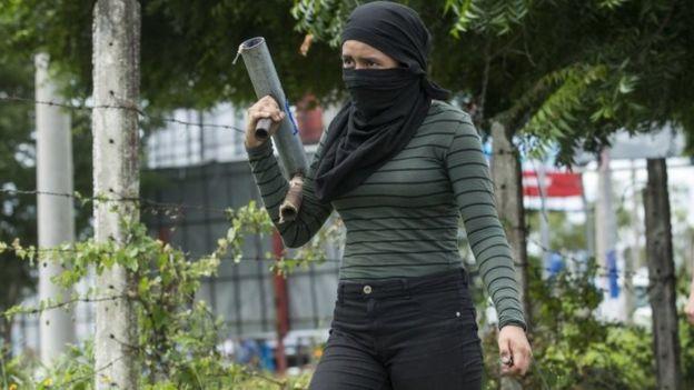 Mulher encapuzada segura morteiro artesanal em protesto na Nicarágua